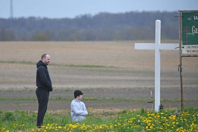 Josh Boggs and his son Bruce, 15 years old, visit the site of the car accident that claimed the lives of three of their family members when the driver of a Ford F-350 failed to stop at a stop sign and slammed into the family's van as they were on their way home from church.