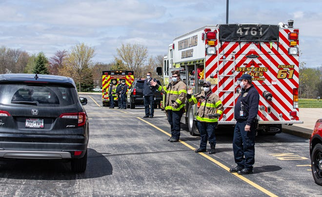 Western Lakes Fire Department and first responders greet students during the family drive-thru event at St. Jerome Parish School in Oconomowoc on Monday, May 4, 2020. The event allowed families to circle through the parking lot and wave to the teachers they have not seen since the pandemic began.