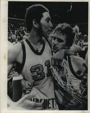 Senior forward Bo Ellis and junior guard Jim Boylan of Marquette exchanged congratulatory hugs while Ellis displayed a souvenir net after Marquette's national championship victory over North Carolina in 1977.
