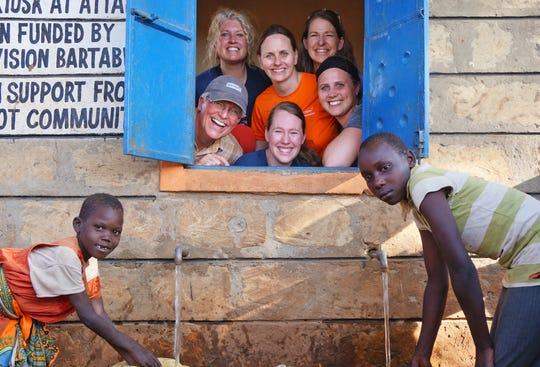 Staci Buck (top row, left) and Kristen Herbst (top row, right) pose for a picture with other volunteers in Bartabwa, Kenya. There, World Vision has helped more than 1,700 households have access to clean water.