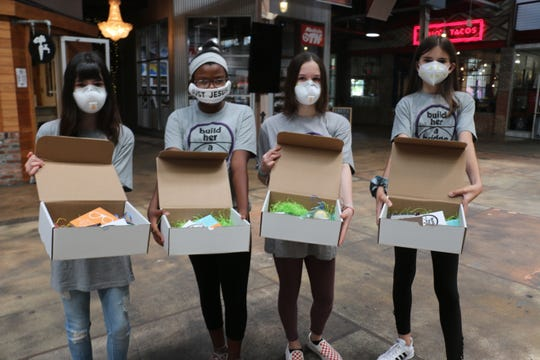 Mia Hawkersmith, Sophia Degrasse, Zoe Hawkersmith and Anna Sgarbi stand together with their boxes they made to help girls and women.