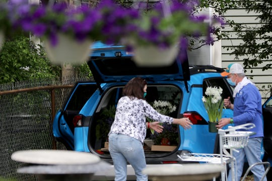 Chris Hanson (right), of Ridgewood, helps a customer load her purchase into a vehicle. Tuesday, May  5, 2020