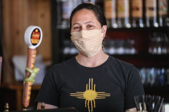 Carol Ayon wears a mask behind the bar at Little Toad Creek Brewery and Distillery in Downtown Las Cruces on Tuesday, April 28, 2020.
