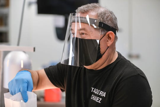 Gonzalo Chavez takes orders while wearing a mask and face shield at Taqueria Chavez in Las Cruces on Wednesday, April 22, 2020.