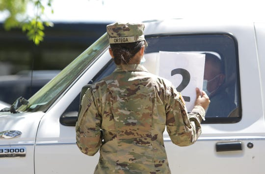 A National Guardsman informs a motorist to call a telephone number as part of the registration process for the free COVID-19 testing site on May 5 at Shiprock High School in Shiprock.