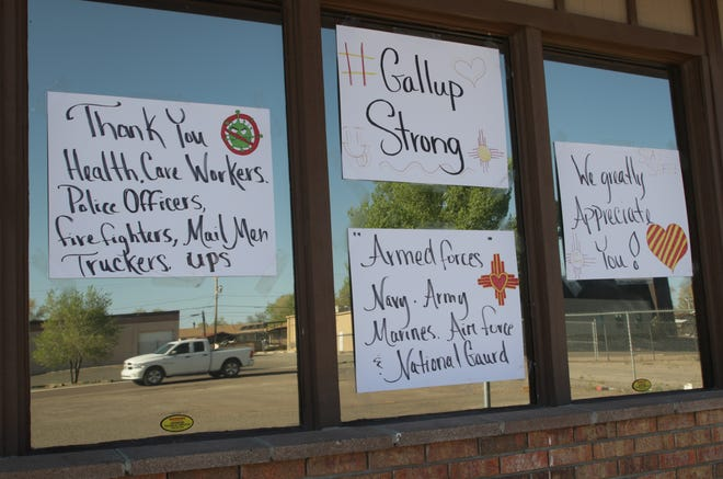 Signs of support for the various professionals working during the coronavirus pandemic are posted on a business in Gallup on May 4. The city has been on lockdown to mitigate the spread of the new virus.