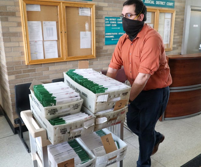 Election worker Jordan Smellip carts some of the nearly 4,000 vote-by-mail ballots Garden City received for the school bond election on May 5, 2020. City hall was open that day for in-person voting as well.