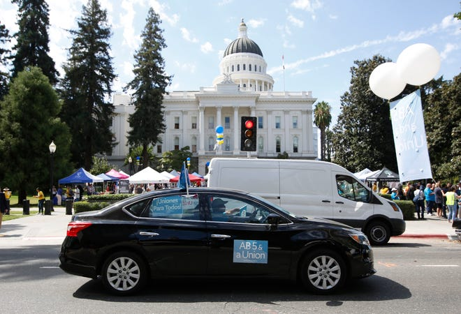 FILE - In this Aug. 28, 2019, file photo dozens of supporters of a measure to limit when companies can label workers as independent contractors circle the Capitol during a rally in Sacramento, Calif. California is suing ride-hailing companies Uber and Lyft, alleging they misclassified their drivers as independent contractors under the state's new labor law, AB5, in effect as of Jan. 1. Attorney General Xavier Becerra announced the lawsuit Tuesday, May 5, 2020, during a news conference. (AP Photo/Rich Pedroncelli, File)