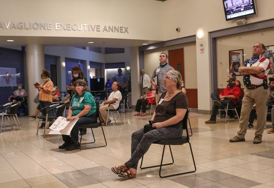 Lauren Crosthwaite, foreground, and other citizens watch the Riverside County Board of Supervisors meeting in an overflow area.  The supervisors were voting on whether to lift the Covid-19 restrictions in Riverside, May 5, 2020.