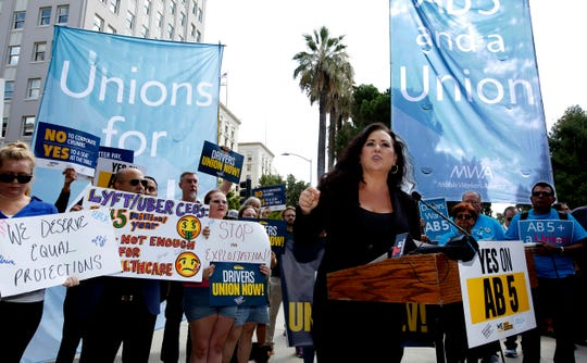 FILE - In this Aug. 28, 2019, file photo Assemblywoman Lorena Gonzalez, D-San Diego, speaks at rally calling for passage of her measure to limit when companies can label workers as independent contractors at the Capitol in Sacramento, Calif. California is suing ride-hailing companies Uber and Lyft, alleging they misclassified their drivers as independent contractors under the state's new labor law, AB5, that took effect Jan. 1. Attorney General Xavier Becerra announced the lawsuit Tuesday, May 5, 2020, during a news conference. (AP Photo/Rich Pedroncelli, File)