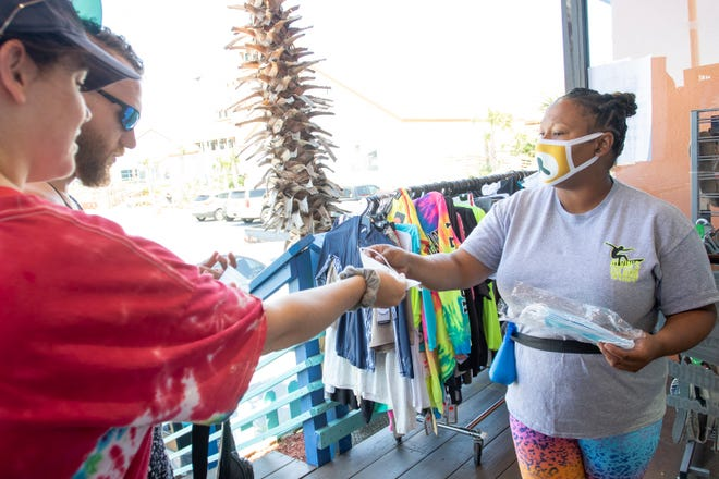 Courtney Mendez-Jones, right, hands face masks to Haley Wachsman and Andrew Rutherford, of Huntsville, Alabama, before they enter Alvin's Island shop at the Pensacola Beach Boardwalk on Tuesday, May 5, 2020.  All customers must wear a face mask to enter the store.