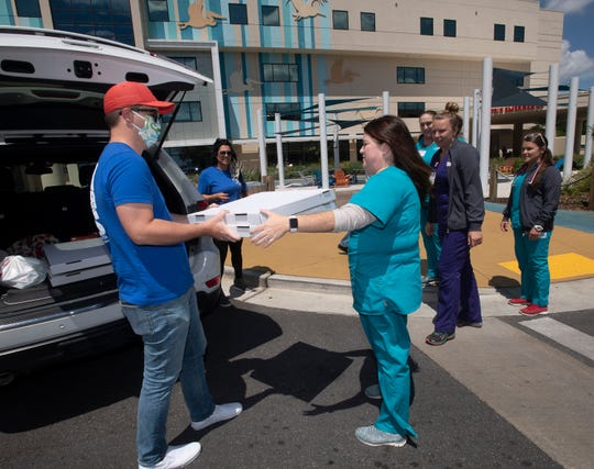 Bradley Sanders from the Gulf Coast Kid's House delivers pizza to emergency room staff at The Studer Family Children's Hospital at Ascension Sacred Heart on Tuesday. The Kids' House made the gesture in recognition of #GivingTuesdayNow.
