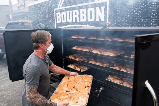 Chuck Messersmith places a tray of chicken leg quarters into a smoker at Bourbon Grill in Hanover on Tuesday, May 5, 2020. Messersmith is the owner of the Grill and also Bourbon Mill, which is located in New Oxford off Route 30.