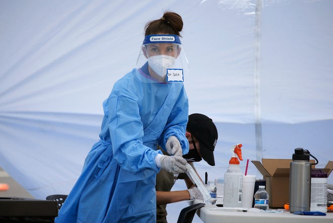 Dr. Sabrina Solt prepares an appointment-only coronavirus drive-thru swab test in the parking lot at Impact Church, Monday, May 4, 2020, in Scottsdale, Ariz. The 2-day testing site for both the coronavirus and the antibody test was made possible by a partnership with Arizona Cardinals' NFL football player Jordan Hicks and Impact Church, hoping to test 500 people.