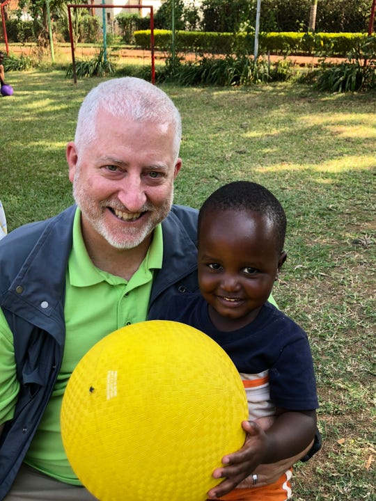 Trent Davis, founder and CEO of Servants, Inc., takes a photo with a young boy during a mission trip in Ethiopia in 2018.