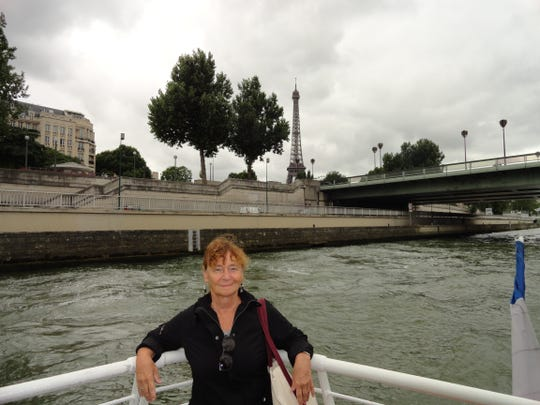 In healthier days, Julie Swope is on the Seine River with the Eiffel Tower in the background. France is one of many journeys she's had in her 72 years.