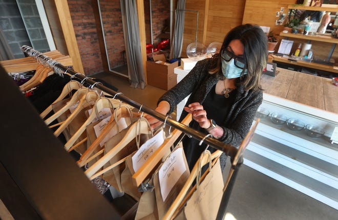 Tanvi Asher, owner at Peppermint Boutique on Culver Road, hangs bags with items waiting for pickup.  Asher has been able to bring back much of her staff during the coronavirus shutdown due to a high volume of online orders.