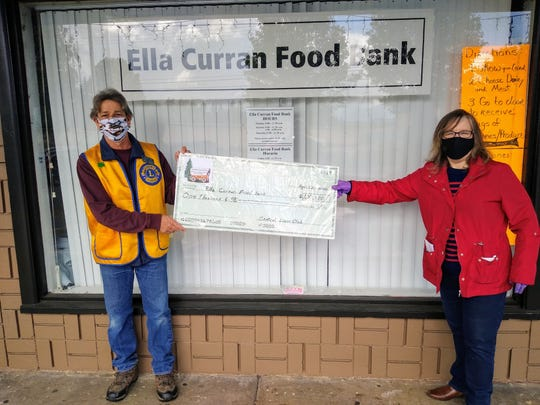Danny Jaffer, left, of Central Lions Club presents a check for $1,000 to Ella Curran Food Bank Director Patty Nevue.