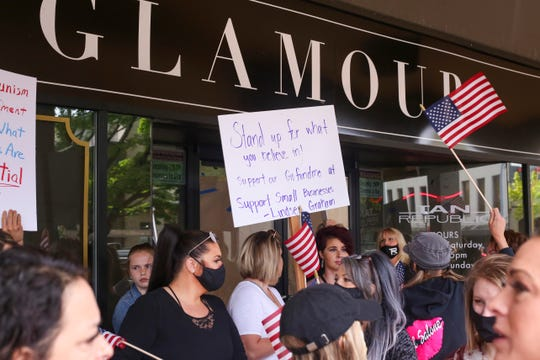 Dozens ofprotesters wave signs and flags to show support for Glamour Salon owner Lindsey Graham, who opened her salon today despite Gov. Kate Brown's stay-at-home order, in downtown Salem on May 5, 2020.
