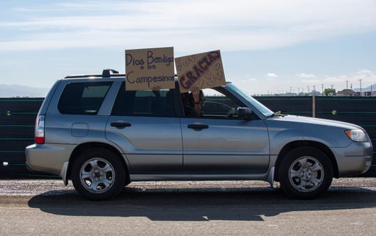 """Two signs are held during the Salinas Valley Caravan of Gratitude on Saturday, May 2, 2020. The sign on the left reads """"Dios bendiga a los campesinos"""" which translates to """"God bless the fieldworkers"""" and the sign on the right reads """"Gracias."""""""