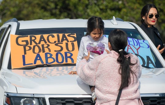 A young girl is placed on the hood of a truck at the Big 5 Sporting Goods parking lot before the start of the Salinas Valley Caravan of Gratitude on Saturday, May 2, 2020.