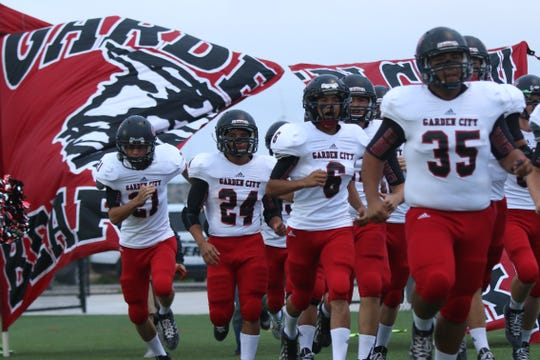 The Garden City High School football team charges onto the field before a game in Sterling City in 2014.