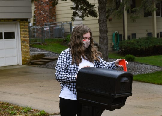 Emerson Weber, 11, sends letters from the mailbox at her house on Tuesday, May 5, in Sioux Falls.
