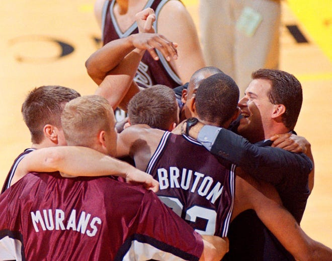 Southwest Missouri State head coach Steve Alford, right, celebrates with Ron Bruton, center, and Paul Murans, left, along with several other teammates Wednesday, Nov. 18, 1998, after they defeated Missouri 72-69 in the first round of the preseason NIT Tournament in Columbia, Mo. (AP Photo/L.G. Patterson)
