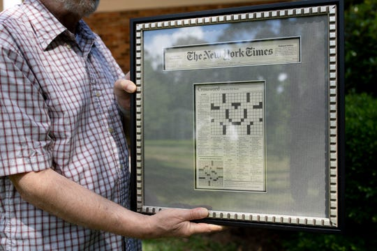 Sande Milton, a New York Times Crossword constructor, holds a framed version of one of the New York Times Crosswords he constructed that appeared in print.