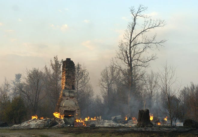 The chimney of a fireplace is all that remains of a home in Big Flats after a fire swept through the area in 2005. About 14 or 15 homes were endangered by the fire, with only three or four fire engines to protect them.