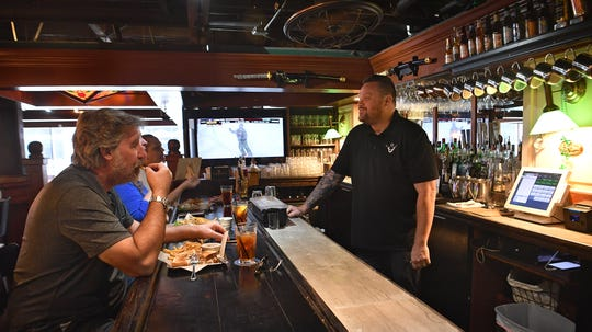 Erik Scott, right, chef of the Highlander Public House, checks on his customers during lunch Tuesday. The restaurant is open and under current COVID-19 restrictions can have up to 25 percent occupancy to help maintain social distancing.