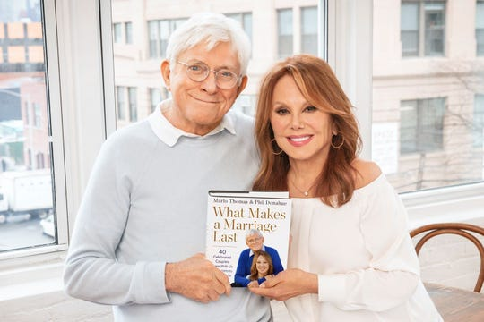 """Phil Donahue and Marlo Thomas hold a copy of their book, """"What Makes a Marriage Last,"""" available now."""