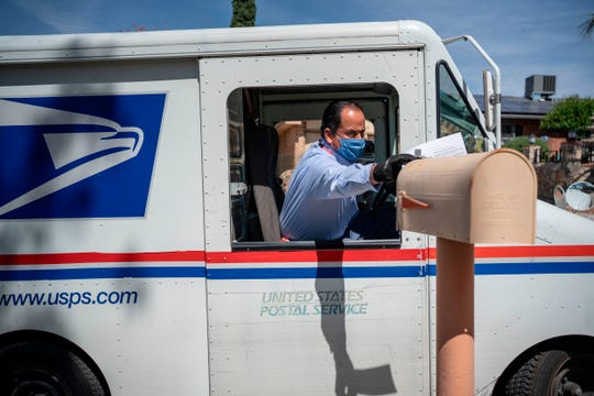 United States Postal Service mail carrier Frank Colon delivers mail amid the coronavirus pandemic on April 30, 2020, in El Paso, Texas.