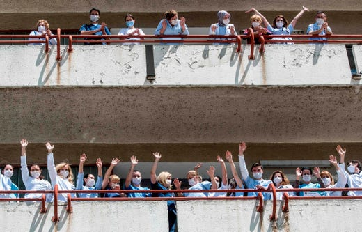 Medical staff claps and waves from the balcony of the Infectious Diseases Clinic in Skopje on May 5, 2020, in support for the invaluable work that nurses and midwives do to ensure clean care for patients, mothers and babies, during the COVID-19 pandemic.