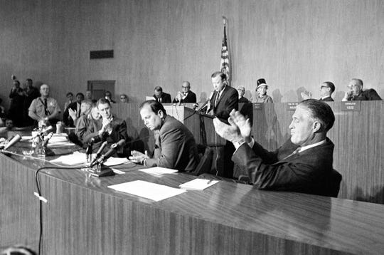 Walter Reuther, President of the United Auto Workers Union (at podium) pledges the help of his union in the rebuilding of the ravaged arms of Detroit, July 27, 1967 to the applause of Gov. George Romney, right. Mayor Jerome Cavanagh, center, Cyrus Vance, next left, President Johnson's personal emissary and Lt. Gen. John Throckmorton, the military commander of the city, left.