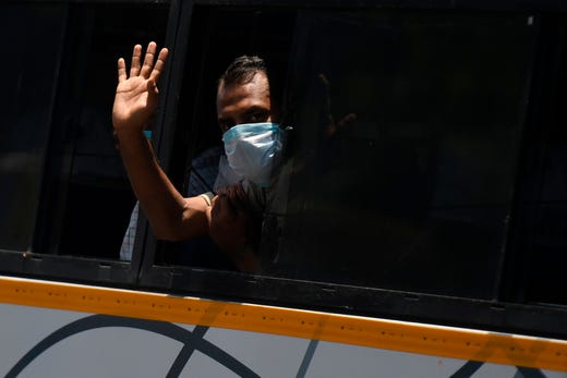 Migrant worker and stranded travellers wave through a window of a bus as they leave to their hometowns after the government eased a nationwide lockdown imposed as a preventive measure against the COVID-19 coronavirus, in Chennai on May 5, 2020.