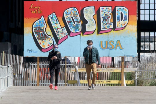 """Danielle Glassman, New Brunswick, and Paul Lavadera, Long Branch, walk along the north end of the Ocean Grove, NJ, boardwalk, May 5, 2020, with a """"Sorry We're Closed"""" sign behind them.  The art is signed by #JackGreenArt and stands on the border with Asbury Park near the Casino building."""