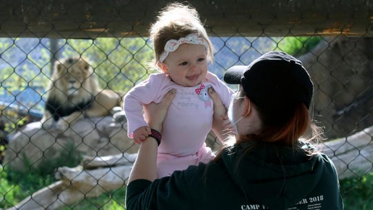 Holly Stuart holds her daughter Savannah during a visit to Utah's Hogle Zoo Saturday, May 2, 2020, in Salt Lake City. The zoo is one of many Utah businesses reopening Saturday amid the Coronavirus pandemic after multi-week closure. The zoo will restrict the number of guests who enter per day to help with social distancing.