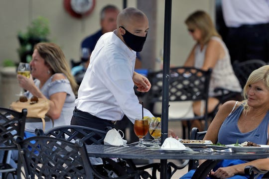 A food server at the Parkshore Grill restaurant wears a protective face mask as he waits on customers, May 4, 2020, in St. Petersburg, Fla. Several restaurants are reopening with a 25% capacity as part of Florida Gov. Ron DeSantis' plan to stop the spread of the coronavirus.