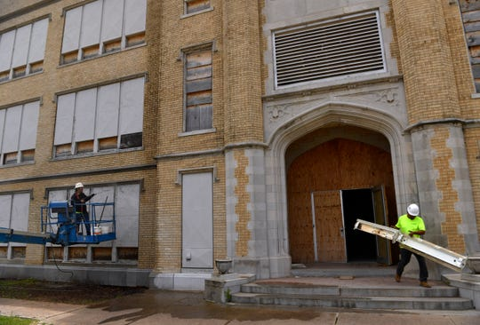 """Irvin """"Scooby"""" Oparka power washes the brick on the Heritage Square building as another worker removes an old light fixture on Tuesday. The former Lincoln Middle School/Abilene High School is being restored as a library and cultural center."""