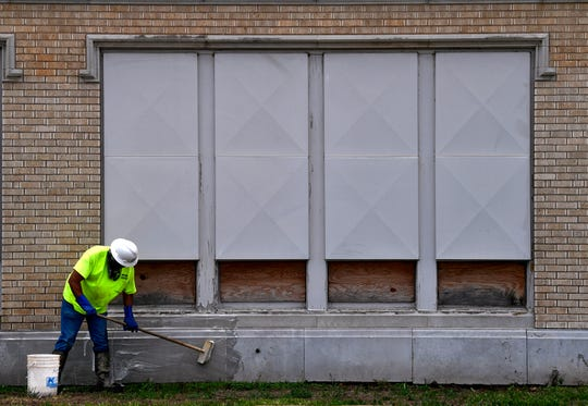 """Andy West of Mid-Continental Restoration Inc. scrubs """"the Lubbock"""" (dirt) off the north side of the former Lincoln Middle School/Abilene High School on Tuesday. West attended Abilene High and said it was an honor to work on the building's restoration."""