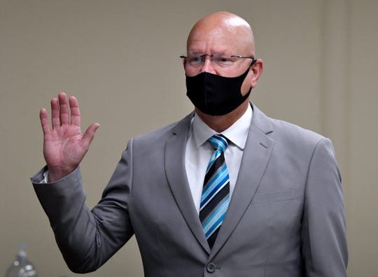 Derek Hood, with mask, takes his oath of office Wednesday. While necessary, it had a strange effect: Is he going to rob a bank after this?