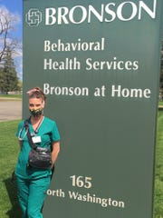 """Katie Sproul, RN, Bronson at Home, wears a """"tool kit"""" when she enters homes and keeps the bag on her at all times to limit potential contamination during the coronavirus outbreak."""