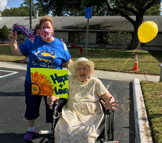 """Eleonor Larsen, holding a 'Hope + Love"""" sign and accompanied by Rose Rogers, waits to see her son and daughter pass by in a """"family parade"""" at Solaris HealthCare on Merritt Island. The parade allowed families to see each other from a distance during the no-visitation guidelines forced by the coronavirus crisis."""