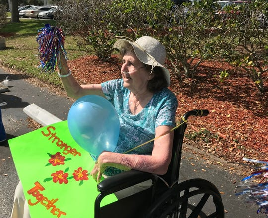 Diana Diamantas waves at family members during a parade at Solaris HealthCare on Merritt Island. The parade allowed families who can't visit during the coronavirus crisis to see each other, from a distance, in the parking lot of the facility.