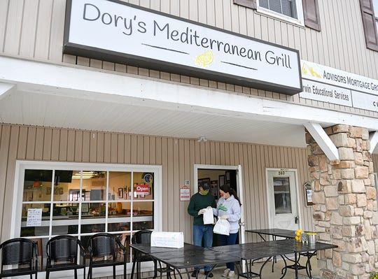 Dory and Christine Chamoun, owners of Dory's Mediterranean Grill in Medford, prepare lunch orders for customers to pickup on Wednesday, May 6, 2020.