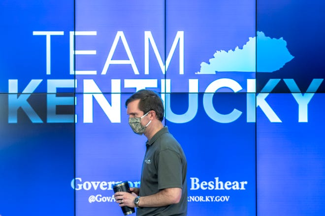 Kentucky Gov. Andy Beshear walks to the podium during a news conference at the state's Emergency Operations Center at the Boone National Guard Center in Frankfort, Ky., to provide an update on the coronavirus situation, Sunday, May 3, 2020.