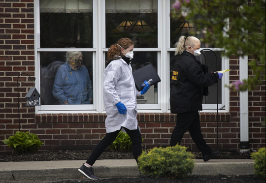 A woman watches from the window as the Ohio Attorney General's office conducts a search of the Bickford assisted living and memory care center in Worthington on Tuesday, May 5.