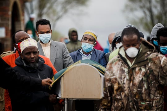 "Siat Bulle, 43, stepfather of Abdullahi ""Abdi"" Sharif, center, helps carry him to his final resting place in the cemetery at the Islamic and Cultural Center Bosniak of Des Moines on Tuesday, May 5, 2020, in Granger. Sharif had been missing since January and his body was found on Saturday in the Des Moines River at Prospect Park."