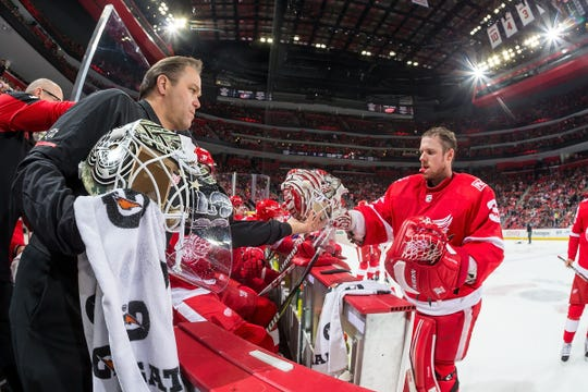 Paul Boyer, head equipment manager for the Detroit Red Wings, talks to players in the bench area during a game.